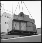 7254 Lading met hulpgoederen voor Mozambique wordt aan boord gehesen van ms. Walvis B. Het betreft een lading brillen ...