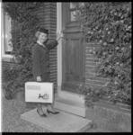 7390-2 Mejuffrouw A.H. Boutelje, hostess van de Felicitatiedienst Nederland, op huisbezoek.
