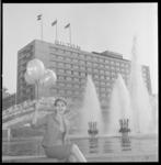7483-2 Fotomodel June poseert op de rand van de fontein aan het Hofplein; op de achtergrond het Hilton Hotel.