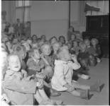 76 Kinderen zittend op de grond in een zaal.