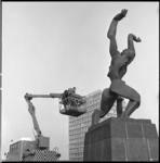 7699 Beeld 'de Verwoeste Stad' op Plein 1940, van Ossip Zadkine, wordt gefilmd. Op de achtergrond het hoofdkantoor van ...
