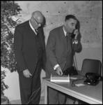 7970-2 Ingenieur R. Diks, hoofddirecteur Telegrafie en Telefonie,knipt als openingshandeling van de telefooncentrale ...