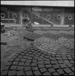 8241 Stratenmakers bezig met sierbestrating op de binnenplaats van de nieuwe 'Doelen'.