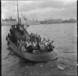 846 Een groep mensen op het achterdek van een sleepboot op de Nieuwe Maas vaart ter hoogte van de Westerkade-Willemskade.