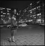 8554 Alleen lopende dame maakt avondwandeling door Aert van Nesstraat bij de Joost Banckertsplaats; op de achtergrond ...