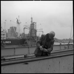 8632-2 Gebarentaal van een havenwerker bij het ruim van een schip in de Maashaven. In de achtergrond een drijvende ...