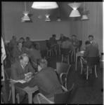 891-2 Zaal met tafeltjes en mensen waar theorie rij-examen wordt gehouden.