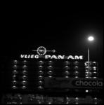 9053-2 Lichtreclame voor luchtvaartmaatschappij PAN AM op een van de Lijnbaanflats en reclame voor Ringers chocolade.