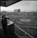 9089-1 Wethouder Minus Polak kijkt over Hofplein en Weenagebied met stationspostgebouw Delftsestraat en in de verte het ...