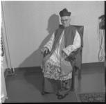 94-2 Mgr. J.H. Niekel gezeten in een stoel.