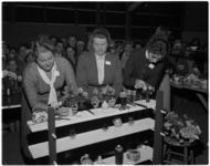 940-2 Bloemschikkende en strijkplank gebruikende deelneemsters aan de wedstrijd 'Wie is de beste huisvrouw van de ...