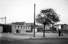 1976-2422 Gezicht vanaf het Stationsplein op een gebouw-en spoorlijn. En een straaturinoir.