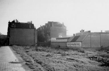 1976-2600 Gezicht op een braakliggend terrein met woningen tussen de Noordsingel en de Almondestraat.