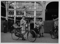 XVII-25-01-02-1 Dames met fietsen en bagage voor de ingang van het Maasstation.