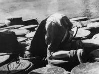 1968-290 Een kind zoekt voedselresten in vuilnisbak tijdens de hongerwinter.