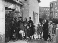 1977-3067 Mensen in de rij voor voedseluitdeling van de centrale keuken of gaarkeuken aan het Grote Visserijplein.
