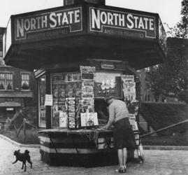 1977-3075 Een kiosk met Duitse propagandalectuur op het Middellandplein. Op de achtergrond een schuilkelder.