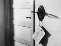 1977-3098 Een muur met op de voorgrond een muurplaat waaraan een weggehaalde telefoon was bevestigd.