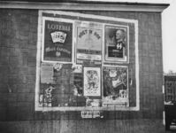 1977-3112 Aanplakbiljetten aan een muur van een noodwinkel, vermoedelijk op de Goudsesingel.