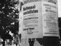 1977-3113 Reclamezuil waarop aanplakbiljetten met propaganda zijn geplakt.