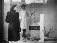 1977-3125 In een etalage wordt reclame gemaakt voor het maken van regenjassen uit lakens: Van slechts 1 laken een ...