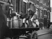 1977-3131 In de Afrikaanderwijk schrappen jongens op een sleperswagen melkbussen leeg die gebruikt worden voor het ...