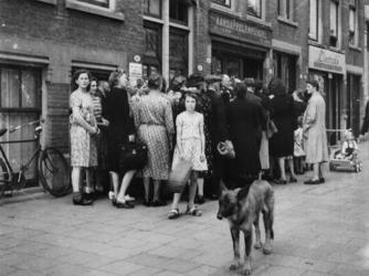 1977-3132 Mensen in de rij bij de aardappelhandel van Jac J. v.d. Veer aan de Vierambachtsstraat.