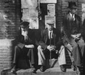 1977-3133 Oudere mannen voor een muur met aanplakbiljetten.
