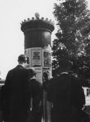 1977-3135 Tijdens de Bezetting van Nederland door de Duitse Weermacht.Tijdsbeeld. Pamfletten en affiches aan aanplakzuil.