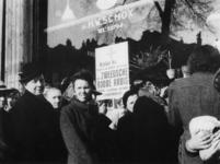 1977-3163 Mensen in de rij voor Zweeds brood bij de kruidenierwinkel van weduwe S.P. Schox-de Haas aan de Oostzeedijk 41a.