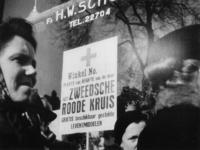1977-3164 Mensen in de rij voor Zweeds brood bij de winkel van weduwe S.P. Schox-de Haas, handel in koloniale en ...