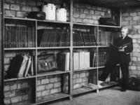 1977-3175 Dirigent Eduard Flipse in een noodruimte waar de overblijfselen van de muziekbibliotheek van het Rotterdams ...