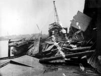 1977-3179 Gezicht op de Maashaven aan de noordzijde met verwoestingen, vernielde loodsen, kademuur, kraan op het ...