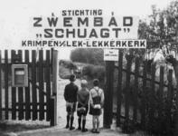 1977-3206 Drie jongens staan met hun opgerolde handdoek bij het hek van Stichting Zwembad Schuagt te Krimpen a/d Lek - ...