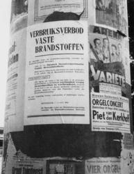 1977-3211 Straatzuil met affiches waaronder een aanplakbiljet met een verbruiksverbod voor vaste brandstoffen.