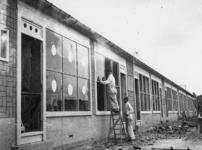 1977-3214 Glazenzetters aan het werk bij noodwoningen van het Brabants Dorp. De nieuwe ruiten worden gemarkeerd met ...