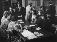 1977-3271 Kinderen (van 8-14 jaar) en ouders bij de administratie voor de kinderuitzending naar de Oostmark in Oostenrijk.