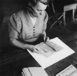1977-3272 Een vrouw bezig met de administratie van de kinderuitzending naar de Oostmark in Oostenrijk.