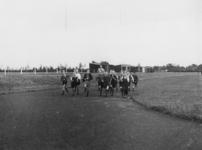1977-3287 Een groepje jongens en een begeleider lopen hard op een atletiekbaan.