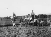 1977-3288 Een groepje bestaande uit (voornamelijk) meisjes en hun begeleiders houden zich op een atletiekbaan bezig met ...