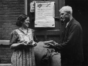 1977-3318 Een huisvrouw ruilt beenderen voor een stuk zeep. Op deur een aanplakbiljet met de aankondiging van de actie ...