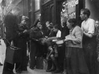 1977-3319 Uitdelen van Engelse biscuits door geallieerde militairen.