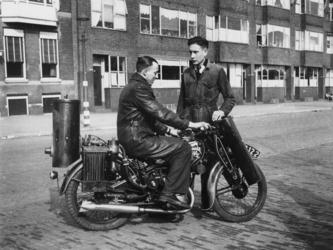 1977-3454 Een motorrijder met een onderhoudsmonteur bij motorfiets met houtgasgenerator.