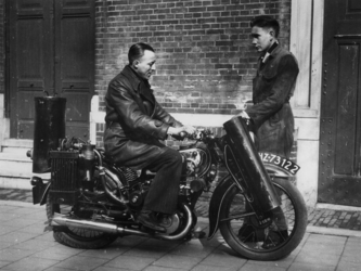1977-3455 Een motorrijder en onderhoudsmonteur bij motorfiets met houtgasgenerator.