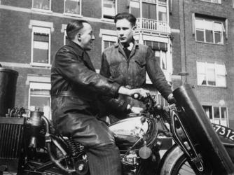 1977-3456 Een motorrijder en onderhoudsmonteur bij een motorfiets met houtgasgenerator.