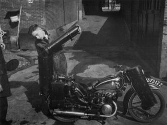 1977-3459 Een motorfiets met houtgasgenerator wordt bijgevuld.