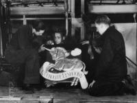 1977-3463 Het gereedmaken van een uithangbord voor een noodwinkel van de Vergulde Eenhoorn aan de Goudschesingel (C 12).