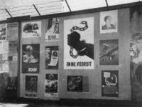 1977-3507 Een schutting met diverse affiches.