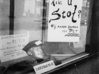 1977-3510 Een kaarten met opschrift: Hebt U stof Wij maken daarvan een pet in de etalage van van een kledingwinkel. De ...