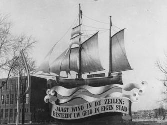 1977-3521 Model van een zeilschip met het opschrift: Jaagt wind in de zeilen: besteedt uw geld in eigen stad.